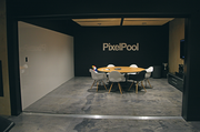 The conference room at PixelPool is off the lobby. The black-themed design provides a dramatic backdrop to the space while reducing visual glare.