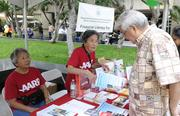 AARP volunteers Audrey Sunada, left, and Ruth Takahashi are seen providing information on products and services to attendees at the Hawaii Department of Commerce and Consumer Affairs Financial Literacy Fair at Tamarind Park in Downtown Honolulu.