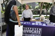 Duane Rhea, senior program analyst for the Internal Revenue Service, provides information on taxpayer advocate services to attendees at the Hawaii Department of Commerce and Consumer Affairs Financial Literacy Fair at Tamarind Park in Downtown Honolulu.