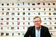 Brian Halligan, co-founder and CEO of HubSpot in Cambridge, MA. in front of a wall of employee profiles.