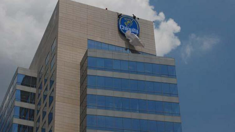 Workers throw off a covering from the Chiquita (NYSE:CQB) sign atop the NASCAR Plaza building.