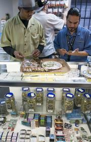 Budtenders Danny Curley, left, and David Marlow, at the Medicine Man growing facility in Denver, roll marijuana joints for sale at the retail counter.