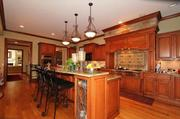 The chef's kitchen has 42-inch cabinetry, a six-burner gas stove with grill, stone accents and a two-tiered island.