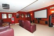 The theater room is equipped with a large screen and projector, plus multiple levels of seating.
