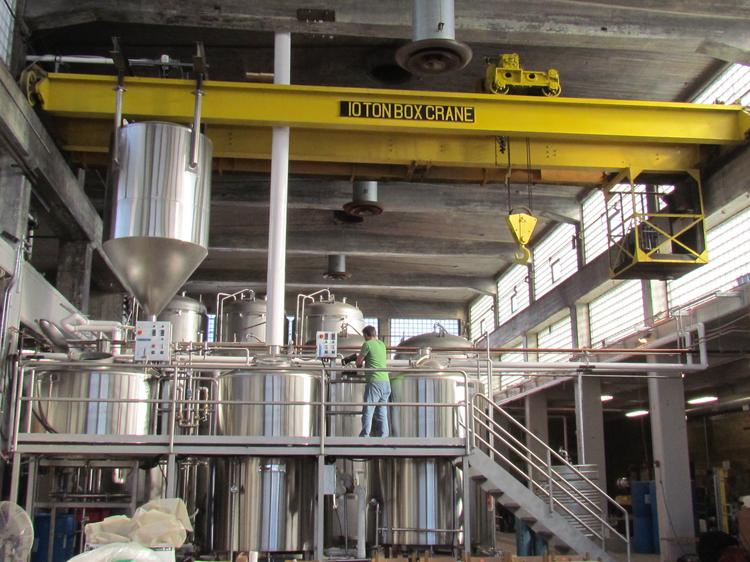 Brewmaster John Haggerty monitors the brewing process at Warped Wing Brewing Company on its first brew day. The brewery hopes to open by February 2014. The 10-ton box crane, original to the building, was moved to function as part of the brewery's setup.