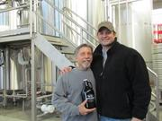 Joe Waizmann, president of Warped Wing Brewing Company, shows off the Warped Wing label on the company's growler with Nick Bowman, who does sales and marketing for the brewery.