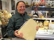 Di Bruno Bros. (930 S. 9th St.) adds to its growing lineup of stores by opening the Franklin building. The site features prepared foods, gourmet coffees, pastries, bread, cured meats and of course cheese. Third-generation owner Bill Mignucci holds up a block of provolone.