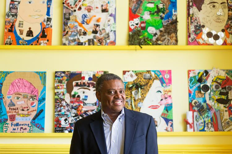 Greg Stewart, CEO of CMIT Solutions of Baltimore, in front of a gallery of student portraits at the Baltimore Lab School. Stewart has donated technology to the school that his daughter graduated from last year and where he still remains on the board.