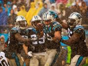 Carolina Panthers linebacker Luke Kuechly exults and is congratulated by teammates after intercepting a Drew Brees pass during a heavy rain storm. This slideshow gives a look at the action.