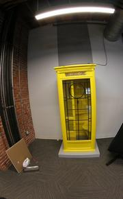 "A yellow phonebooth in the ""hangout"" space of the accelerator."