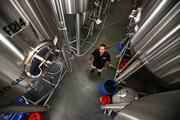 Joey Redner, owner of Cigar City Brewing, between fourteen 3,720-gallon fermenters in the brewery's new building.