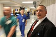 Largo Medical Center's Anthony Degina, CEO, stands in a busy ER hallway as Steve Raisch, Tech EMT and Kelly Greenwood, RN hurry by.