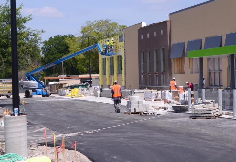 Construction crews at work on storefronts at the Market at Southside shopping center.