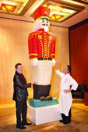 Boston Ballet Artistic Director Mikko Nissinen, (L), admires a giant Gingerbread Macaron Nutcracker created by Ritz-Carlton Boston Common chef Andrew Yeo and his pastry team.