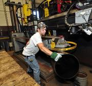 Mark Case, Jr. uses a seamless welder to make a drum at Hannay Reels, Inc. in Westerlo, NY.