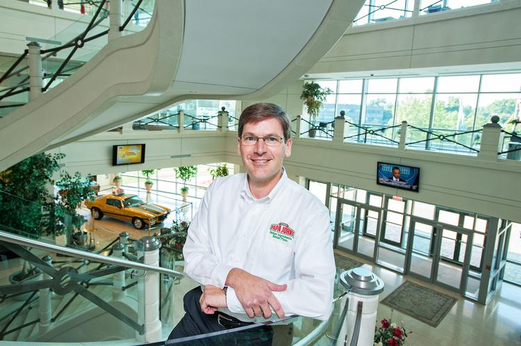Tony Thompson, president of Pap John's International Inc. is shown in the atrium of the company headquarters where John Schnatter's car is on display.