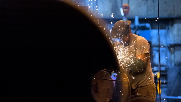 A welder at Caldwell Tanks works on a column for an elevated tank.