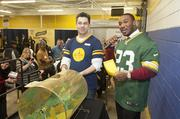 Scott Marshall of the Hunger Task Force and Franklin pull a winning entry for tickets to a Packers game.