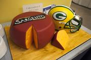 A local baker/artist created a Sargento Foods wheel cake and a Packers helmet cake for the event.