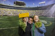 Sarah McVey and Cindy Eggleston of the Mukwonago Food Pantry pose in front of a photo of Lambeau Field and Packers quarterback Aaron Rodgers.