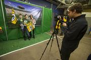 Robin Widauer, her son, Samuel, and Claudia Rimmer of Hope Lutheran pose in front of a photo of Lambeau Field for photographer Nick Heckman.