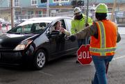 Traffic controllers offer directions to a driver navigating around the construction under the Alaskan Way Viaduct.