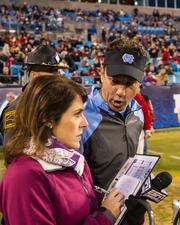 North Carolina Tar Heels head coach Larry Fedora gives a quick interview to ESPN Radio before the start of the second half. The Tar Heels beat the Cincinnati Bearcats 39-17 in the 2013 Belk Bowl, played Dec. 28, 2013 at Bank of America Stadium in Charlotte.