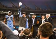 North Carolina Tar Heels head coach Larry Fedora holds the Belk Bowl trophy aloft. To his right is defensive end Kareem Martin, and behind him, partially visible, is the game's most valuable player, Ryan Switzer. To Fedora's left are Johnny Belk, Tim Belk (chairman and CEO of Belk Inc.) and Will Webb, executive director of the Belk Bowl. The Tar Heels beat the Cincinnati Bearcats 39-17 in the 2013 Belk Bowl, played Dec. 28, 2013 at Bank of America Stadium in Charlotte.