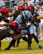 North Carolina wide receiver Quinshad Davis is swarmed by Cincinnati Bearcats tacklers. The Tar Heels beat the Bearcats 39-17 in the 2013 Belk Bowl, played Dec. 28, 2013 at Bank of America Stadium in Charlotte.