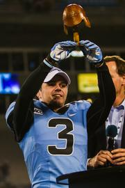 North Carolina Tar Heels wide receiver Ryan Switzer holds his Belk Bowl MVP trophy aloft. Switzer's biggest play was an 86-yard punt return for a touchdown. The Tar Heels beat the Cincinnati Bearcats 39-17 in the 2013 Belk Bowl, played Dec. 28, 2013 at Bank of America Stadium in Charlotte.