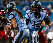 North Carolina Tar Heels quarterback Marquise Williams hands off to tailback Khris Francis. The Tar Heels beat the Cincinnati Bearcats 39-17 in the 2013 Belk Bowl, played Dec. 28, 2013 at Bank of America Stadium in Charlotte.