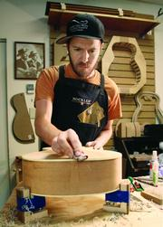 Raymond Morin, retail manager and repairman at Acoustic Music Works in Squirrel Hill, sands the binding on his handcrafted guitar, his fifth such instrument. Morin is a certified luthier and also a guitarist.