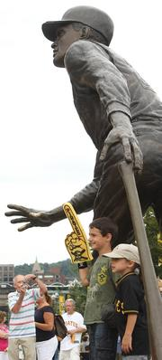 Fans pose with the Roberto Clemente statue outside of PNC Park Aug. 2, 2013, prior to the Pirates-Rockies game.