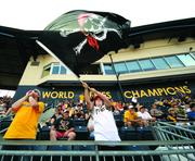 "Austin McCoy, 13, of Freedom, Beaver County, waves the Jolly Roger late in the Pirates-Marlins game Aug. 8, 2013, at PNC Park. Austin's father, Jess, 42, at left, was only nine years old when the Pirates last won a World Series, in 1979.  ""I didn't watch it, "" the elder McCoy said. ""But I remember my dad watching it."""