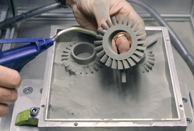 Production service center technician Rick Gabonay uses compressed air to remove loose, nonprinted powder from parts produced by an R2 additive printing machine at The ExOne Co., a 3-D printing company.