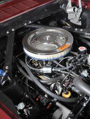 Close-up under the hood of 1965 red Ford Mustang.