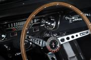 Behind the wheel of 1965 Caspian Blue Ford Mustang.