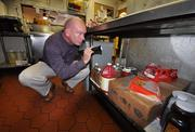 Brian Petty, branch manager for Truly Nolen, conducts a routine cleanliness check at a Coral Springs restaurant.