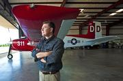 Chuck Schnatter stands near his plane in a hanger at Bowman Field.