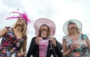 Elena Russo, Joy Kenny and Nicole Northrop watch as a WWII B-25 bomber flies over the infield during Preakness at Pimlico Race Track.