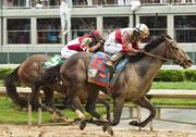 Orb, ridden by Joel Rosario, is about to cross the finish line and win the 139th Kentucky Derby.