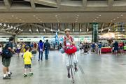 A woman on a unicycle rides around the Family Fun Zone during day 1 of the 2013 Grand Prix of Baltimore.