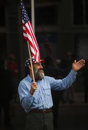 Dave Kannapell waves at the UAW 862/Ford Motor Co. Veteran's Day Parade processional as it moves down Fourth Street, from Chestnut Street to Main Street. Kannapell, whose father served in World War II, said he was attending the parade to support both his family and veterans as a whole.