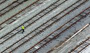 Shot from a balcony atop Silo Point, a track worker walks the rails in Locust Point.