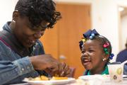 Trina Collins, 28, shares a laugh with her daughter, Nautica, during lunch between classes at the Community Works program at Bon Secours hospital in West Baltimore.