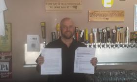 Jeff Britton, the founder of Exit Six stands behind his bar holding the original letter from Starbucks and his response.