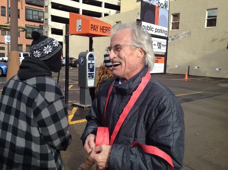 1617 Wazee St. building owner Donald C. Andrews hands out tickets for retail marijuana customers waiting in line Wednesday at LoDo Wellness Center.