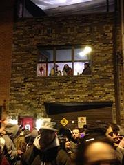 2nd Street residents watch the revelry from their windows.