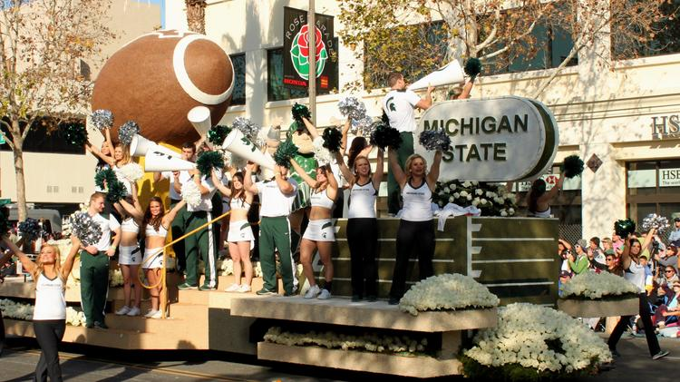 Michigan State cheerleaders ride a float in the Tournament of Roses parade.