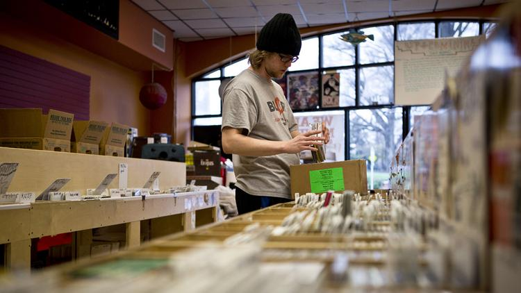 Kyle Rosko, an employee at Schoolkids Records on Hillsborough Street in Raleigh, helps pack CDs into boxes for the store's move to a new location at the Mission Valley Shopping Center in January 2014.
